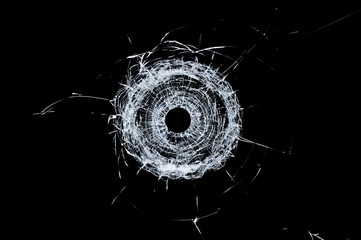 Broken glass single bullet hole in glass isolated on black