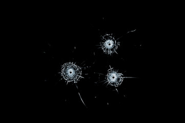 Broken glass triple bullet holes in glass isolated on black