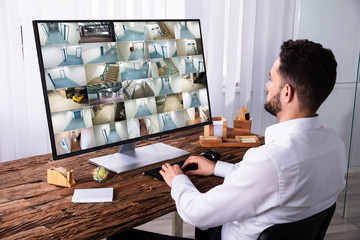Businessman Monitoring CCTV Camera Footage On Computer