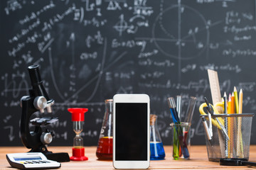 School supplies. Tubes with chemical liquids stand on a wooden table on a chalkboard background