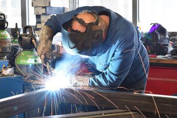 Schweißer in einer Werkstatt bei der Konstruktion und Herstellung von Bauteilen aus Metall // welder at work