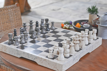 A set of stone handmade chess on a wooden table in the living room