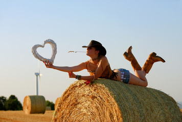A young woman dressed as a cowgirl lies on a hay bale at sunset.  She holds a straw heart in her hand  and shows off her happiness for  wind technology and the windmills turning behind her.