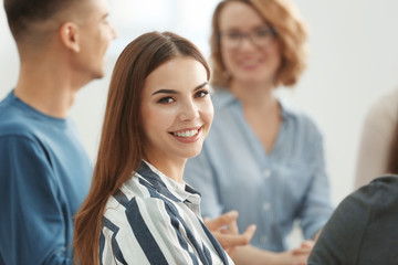 Young woman at group psychotherapy session indoors