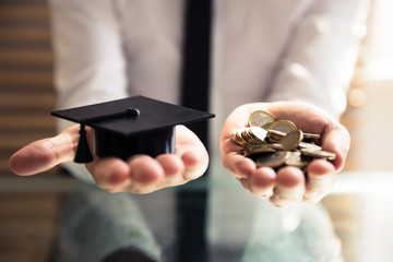 Human Hand Holding Graduation Hat And Golden Coins