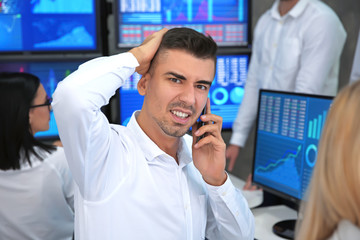Displeased male stock trader talking by cellphone on office