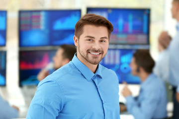 Happy male stock trader in office