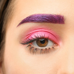 Young woman with dyed eyebrow and creative makeup on dark background, closeup