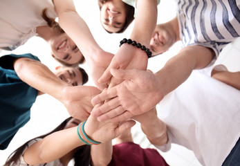 People putting hands together indoors, view from below. Unity concept