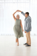 Adorable mature couple dancing together indoors against window
