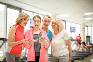 Young coach with phone and group of mature women in modern gym