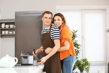 Cute young loving couple cooking in kitchen
