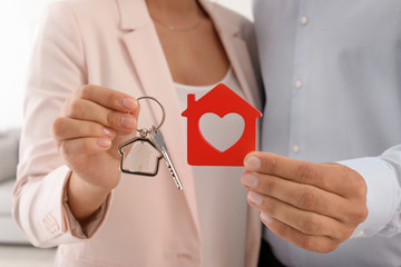 Young couple holding key and house model, closeup. Real estate agent services