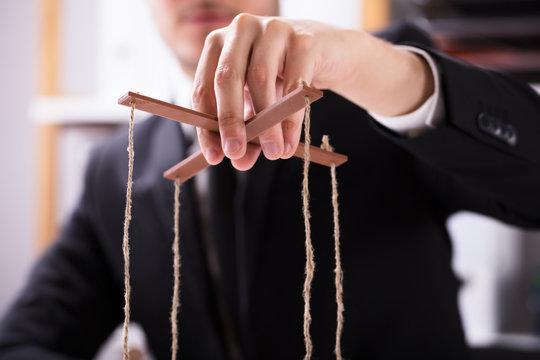 Businessperson Manipulating Marionette