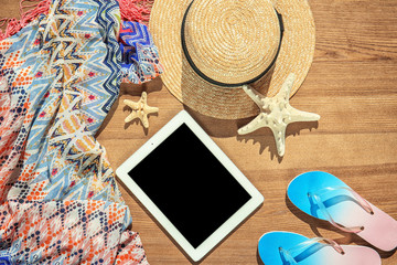 Flat lay composition with tablet and beach objects on wooden background
