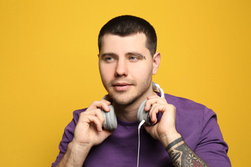 Young man with pierced eyebrow and headphones on color background