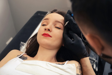 Professional tattoo master applying permanent makeup on eyebrows in salon