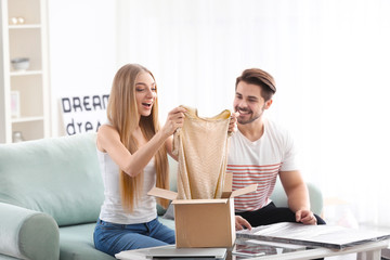 Young couple unpacking parcel at home