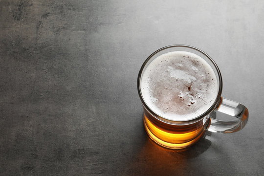 Glass mug with cold tasty beer on grunge background, view from above