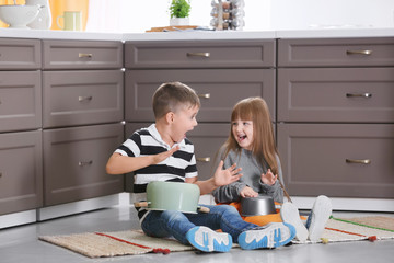 Cute little musicians playing drums on kitchenware at home