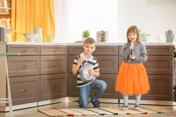Cute little children playing as musical band in kitchen