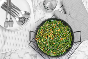 Yummy green beans with almonds in serving pan on table
