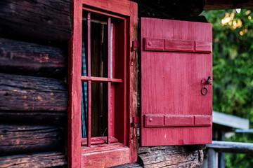 Rotes Fenster an rustikaler Holzhütte