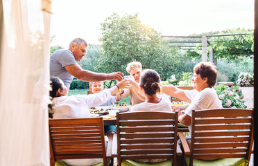 Three generations one family  have dinner in summer garden