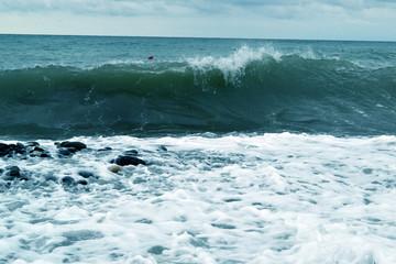 blue ocean wave breaks along the shore