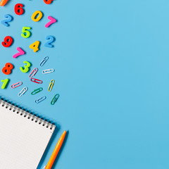 Notebook, pen, colorful numbers on blue background.