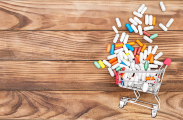 Shopping cart with pills on wooden background. Space for text. Medical background.