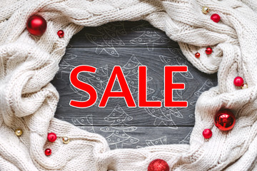 """Christmas banner """"Sale"""" with knitted scarf on grey rough wooden background. Traditional rustic decor for new year holidays and creative chalk doodles. Flat lay, top view, copy space."""