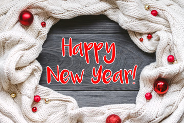 """Christmas card """"Happy New year"""" with frame decorated with knitted scarf on grey rough wooden background. Flat lay, top view, copy space."""