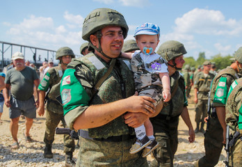 A Russian serviceman holds a boy after the Open Water competition for pontoon bridge units, as part of the International Army Games 2018, outside Murom
