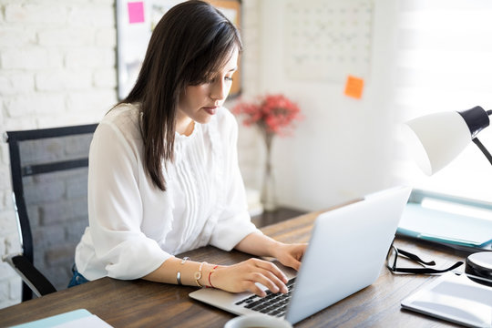 Latin businesswoman working at her desk