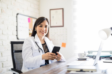 Happy young doctor with phone at office