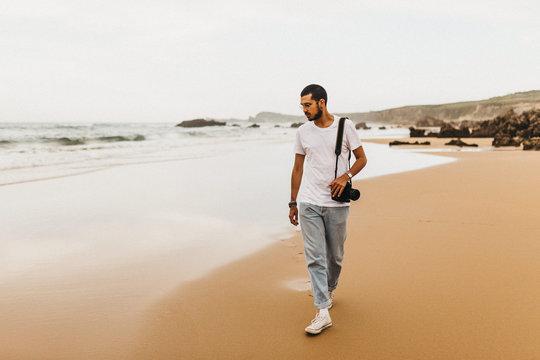 Man with camera walking on beach