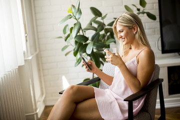 Young woman using mobile phone and holding glass of water in the living room