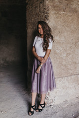 Young woman near wall in old building