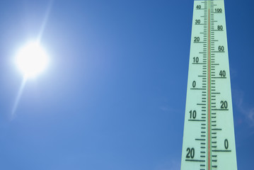 Thermometer with a temperature of +40 degrees Celsius on a background of bright sun and blue sky
