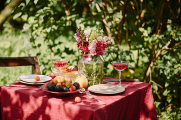 fruits, wineglasses and bouquet of flowers on table in garden