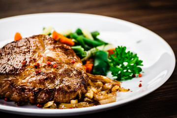 Grilled steak with vegetables on wooden background