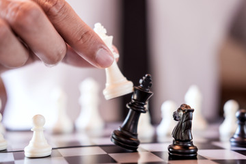 Hand of confident businessman use king chess piece white playing chess game to crash overthrow the opposite team and development analysis new strategy plan, business strategy for win and success Wall mural