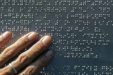 The fingers are touching the metal plate written in the Braille letters; helps the blind to recognize and communicate through the text.
