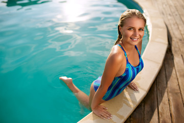 Fashion photo of attractive slim woman with long blond hair in elegant striped body swimsuit relaxing in swimming pool at tropical resort. Wet girl posing in water. Young female walks out the pool.