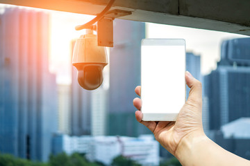 cctv camera device install with downtown building background security ideas concept with hand hold smartphone blank screen
