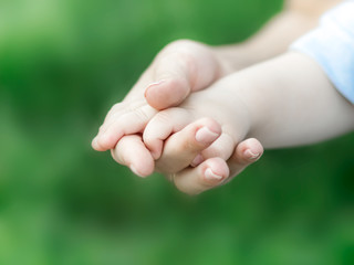 Young caucasian mother holding hand of newborn baby on green grass blurred background. The concept of mother love, care and health. Human body parts