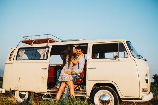 Couple kissing and embracing at van