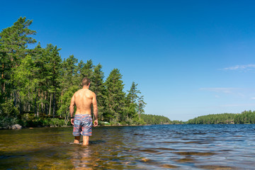 Fit man goes into a swedish lake to swim