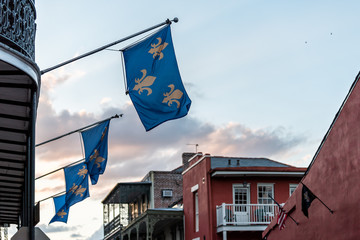 New Orleans old town Bourbon street in Louisiana famous town, city, blue flags hanging off balcony wall, nobody at dark evening sunset, architecture, clouds in sky, flag